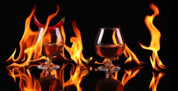 Papryczka chili w szklance brandy z ogniem na czarnym tle