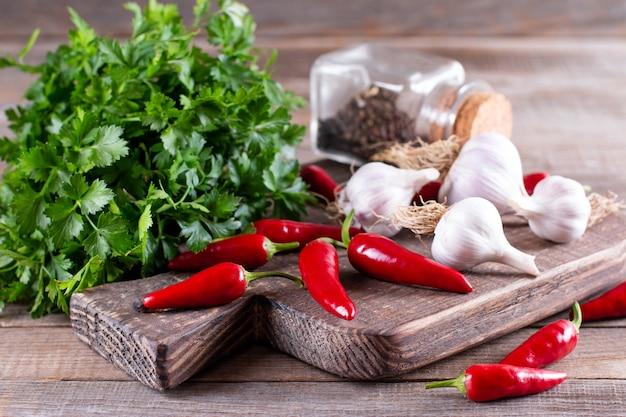 Papryczki chili, czosnek, zioła - przyprawy naturalne. zioła i przyprawy na drewnianej desce