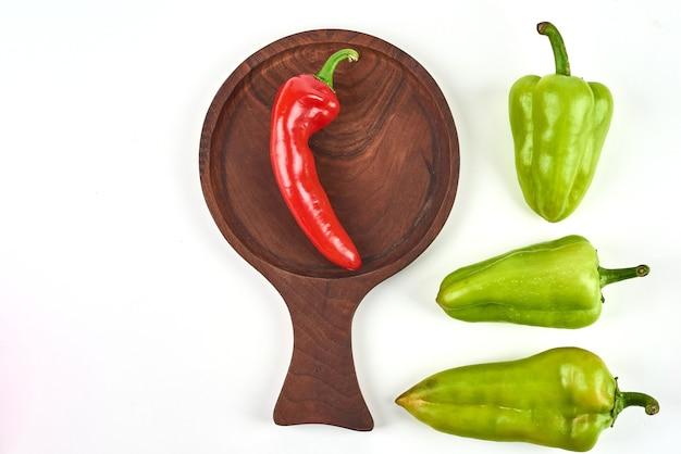 Papryczki chili w drewnianym talerzu.
