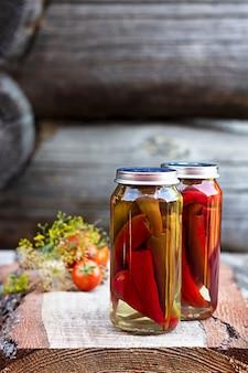Papryczki chili w szklanym słoiku na drewnianym stole, domowe pikle