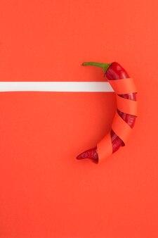 Papryczki chili zawinięte w czerwony papier na czerwono