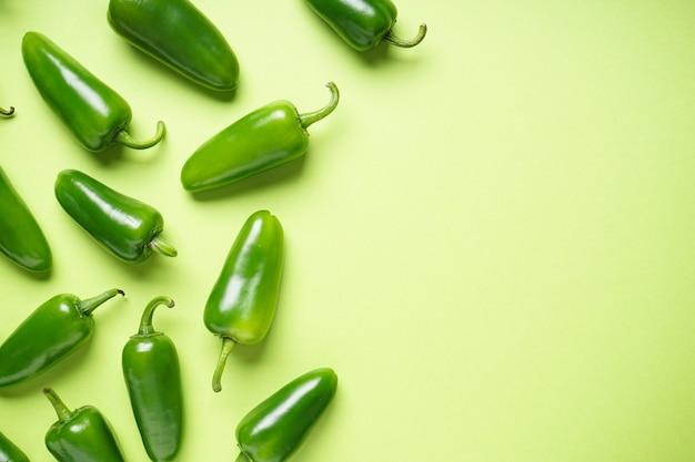 Papryczki jalapeno chili, na zielonym tle, miejsce na tekst. widok z góry.