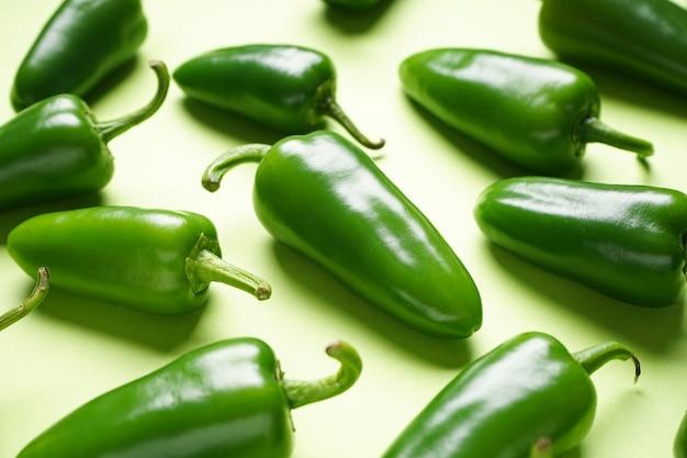 Papryczki jalapeno chili, na zielonym tle, zbliżenie.