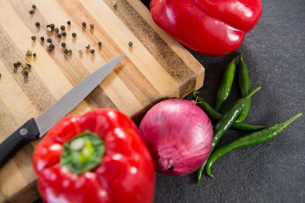Papryka, cebula, chilli i nóż na desce