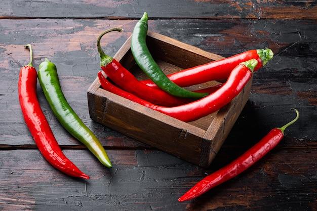 Papryka chili czerwony i zielony zestaw, w drewnianym pudełku, na ciemnym tle drewniane