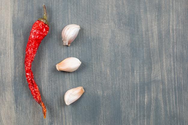 Papryka chili i segmenty czosnku na drewnianym stole