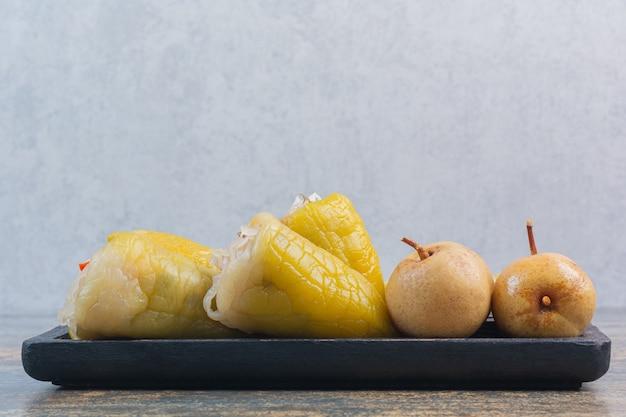 Papryka i jabłko zakonserwowane na drewnianym talerzu, na marmurze.