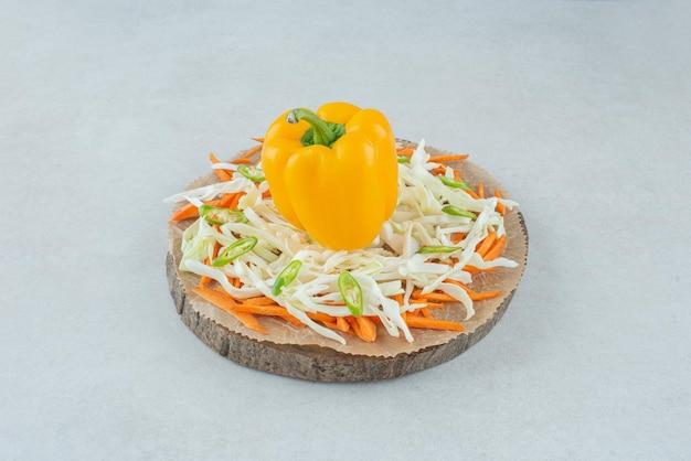 Papryka i posiekane warzywa na drewnianym kawałku.