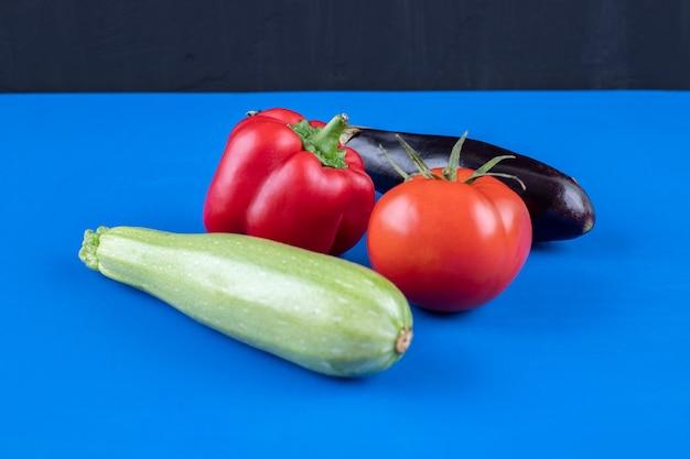 Papryka, pomidor, bakłażan i cukinia na niebieskiej powierzchni