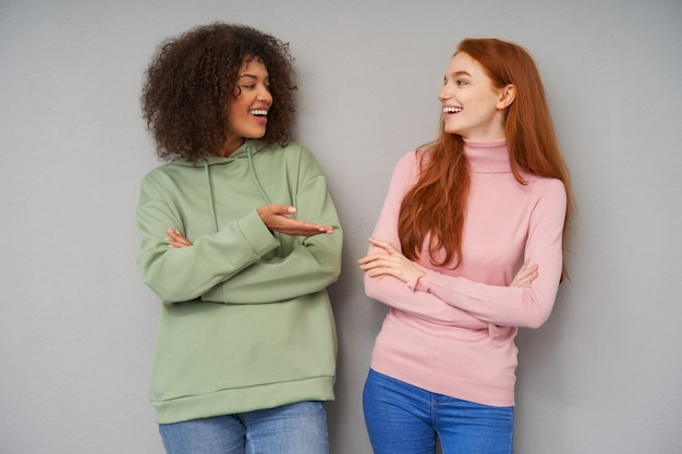 Para atrakcyjnych pozytywnych kobiet, które są w dobrym nastroju i prowadzą miłą rozmowę, stojąc nad szarą ścianą, patrząc na siebie radośnie i szeroko się uśmiechając