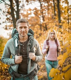 Para backpackers idąc przez las jesienią