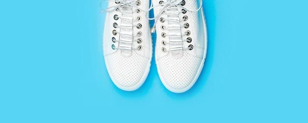Para białych butów na niebieskim tle. trampki na białym tle na niebieskim tle, moda. białe buty. ujęcie z góry butów do biegania. bliska, modne buty wykonane ze sznurowadeł. skopiuj miejsce.