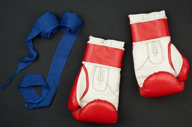 Para białych i czerwonych skórzanych rękawic bokserskich i niebieskiego tekstylnego bandaża