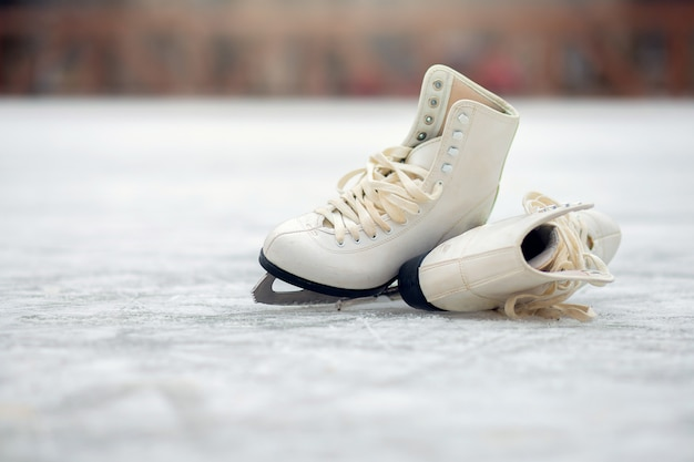 Para białych łyżew figurowych leży na otwartym lodowisku