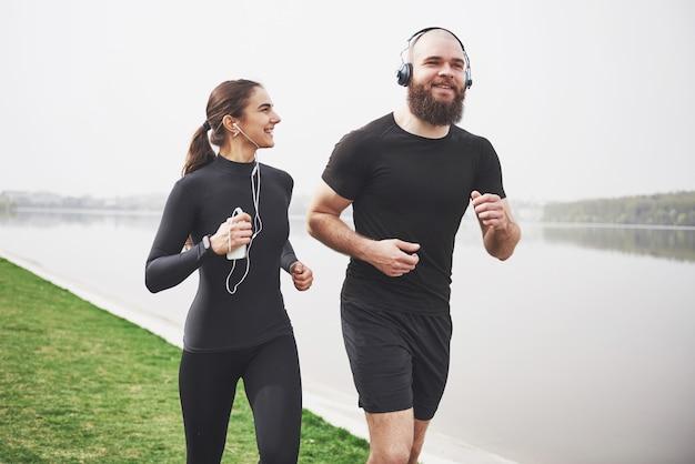 Para bieganie i bieganie na świeżym powietrzu w parku, w pobliżu wody. młody brodaty mężczyzna i kobieta razem ćwiczenia rano