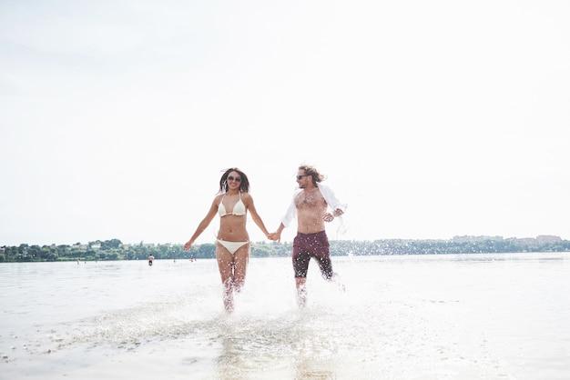 Para biegnąca wzdłuż wody, piękna letnia plaża.