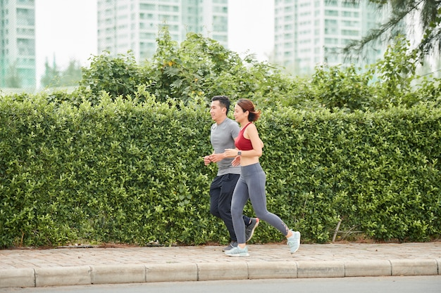 Para biegnie wzdłuż ogrodzenia