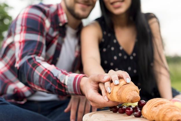 Para bierze croissant w parku