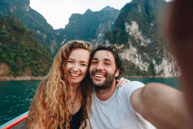 Para bierze selfie na longtail łodzi