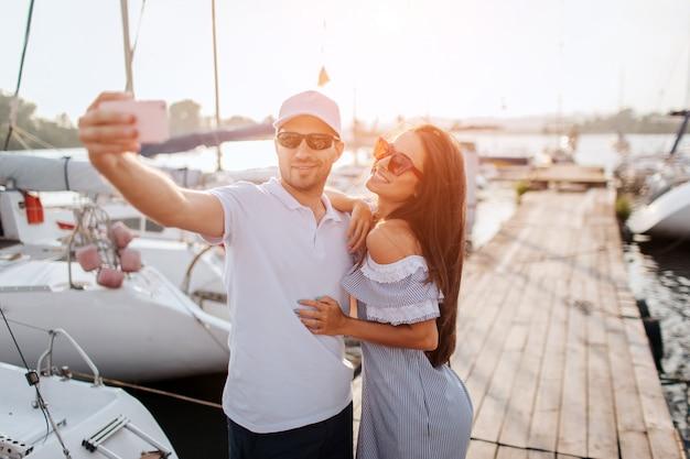 Para bierze selfie na molu. młody człowiek trzyma telefon, podczas gdy brunetka się uśmiecha. pochyla się blisko siebie. każdy z nich ma okulary przeciwsłoneczne. stoją na molo między jachtami. słońce zachodzi.