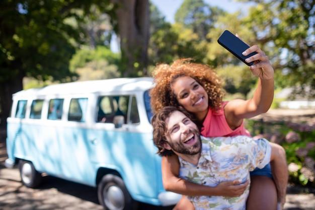 Para bierze selfie podczas gdy cieszący się piggyback przejażdżkę