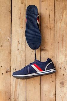 Para butów sportowych wisi na gwoździu na drewnianej ścianie