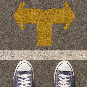 Para butów stojących na drodze z dwukierunkowa żółta strzałka