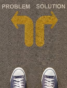 Para butów stojących na drodze ze strzałką