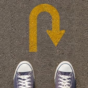 Para butów stojących na drodze ze znakiem ruchu