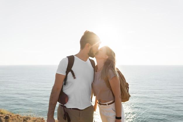 Para całuje się na wybrzeżu o zachodzie słońca