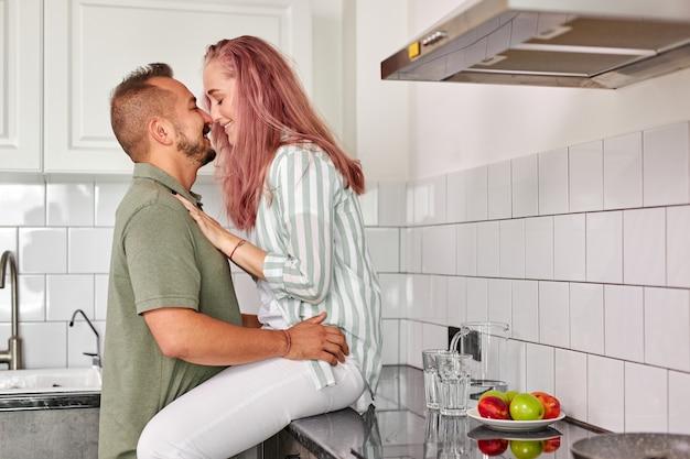 Para całuje się w kuchni z jasnym wnętrzem na poddaszu, romantyczny czas, weekendy, w domowych ubraniach