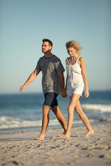 Para chodzi wpólnie ręka w rękę na plaży