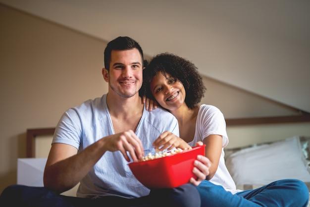 Para cieszy się dzielić czas w domu z filmem i popkornem.