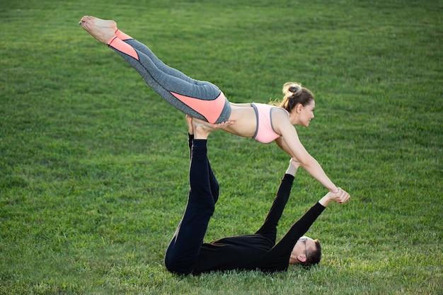 Para ćwiczy acro jogę w parku na trawie