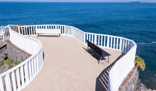Para czarno-białych ławek z widokiem na morze w miejscowości candas