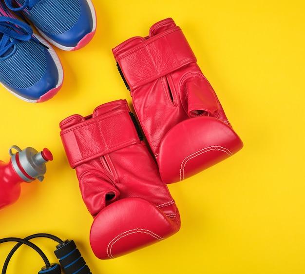 Para czerwone rękawice bokserskie i niebieskie trampki, widok z góry
