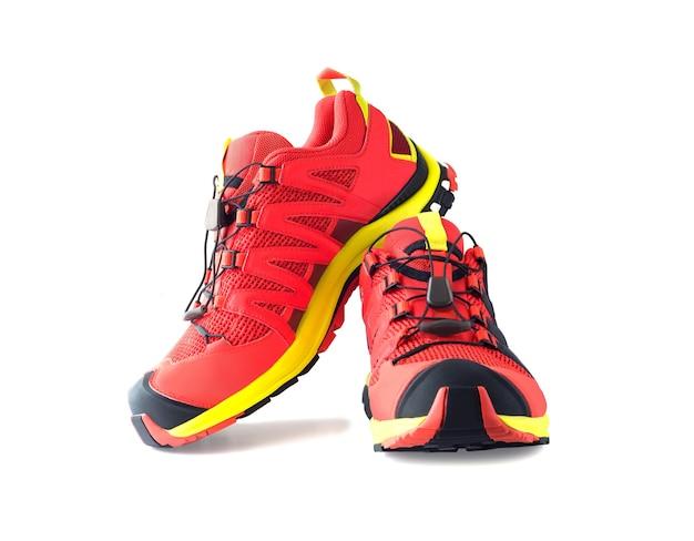 Para czerwonych butów do biegania w terenie na białym tle