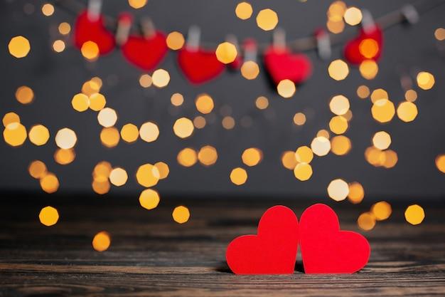 Para czerwonych serc na tle światła, koncepcja miłości i valentine na drewnianym stole
