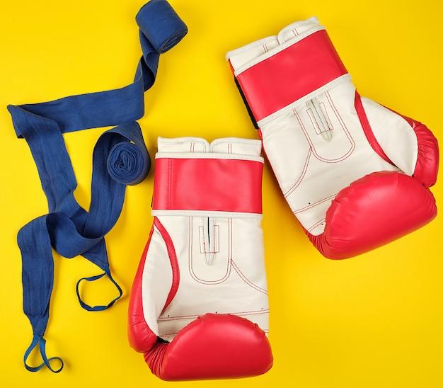 Para czerwonych skórzanych rękawic bokserskich i niebieskiego bandaża tekstylnego,