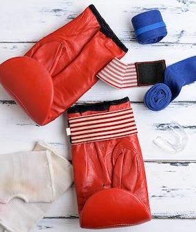 Para czerwonych skórzanych rękawic bokserskich, niebieski bandaż tekstylny