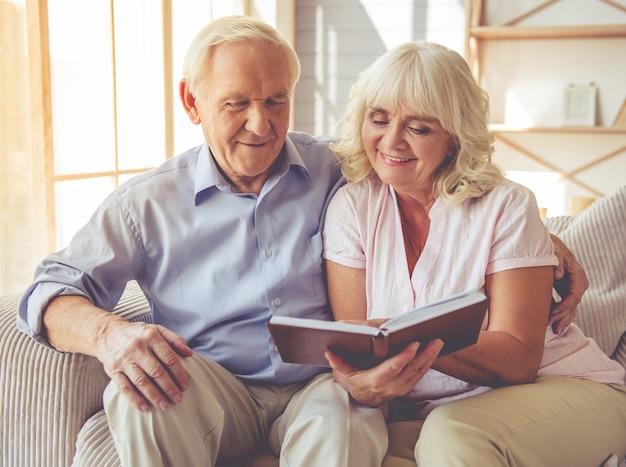 Para czyta książkę i uśmiecha się, siedząc na kanapie