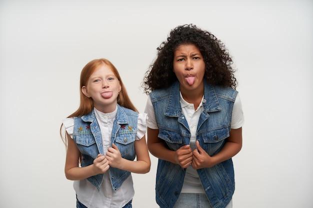 Para długowłosych młodych kobiet w codziennych ubraniach trzymających się za ręce na kamizelkach i pokazujących język, oszukując i robiąc miny podczas pozowania na biało