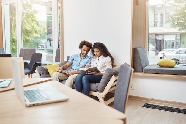 Para dobrze wyglądających wieloetnicznych studentów sztuki w zwykłych ubraniach, siedząca wygodna sofa w dużej jasnej bibliotece, czytająca informacje o historii filmu w książkach i przygotowująca się do egzaminu.