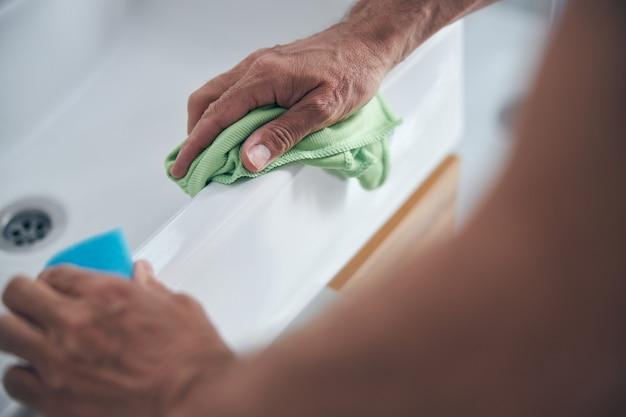 Para dojrzałych męskich dłoni trzymających gąbkę i szmatkę