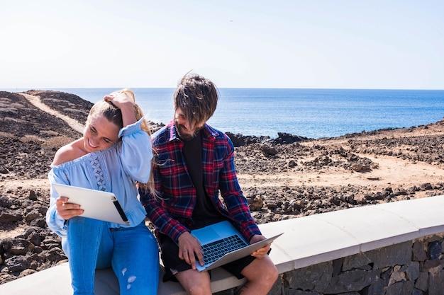 Para dorosłych korzystających z laptopa i talet wraz z plażą w tle - dwie osoby uśmiechnięte i dobrze się bawiące - mężczyzna używający i piszący na komputerze i kobieta korzystająca z tabletu