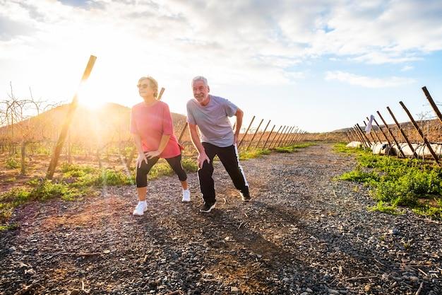 Para dorosłych seniorów uprawiających sport rano, aby zachować zdrowie i życie przez długi czas - fitness i rozciąganie dla starszego społeczeństwa - ludzie wykonujący zajęcia fitness na świeżym powietrzu