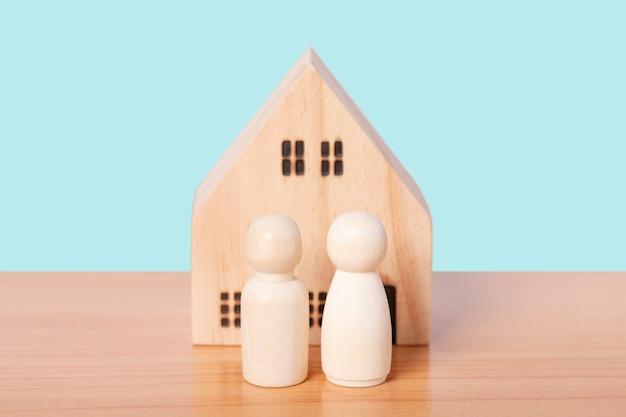 Para drewnianych lalek stoi przed modelem domu na niebieskim tle. dom rodzinny, ubezpieczenia i nieruchomości inwestycyjne koncepcja nieruchomości.