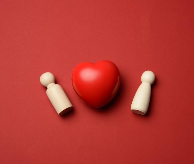 Para drewnianych mężczyzn panny młodej i pana młodego, między nimi czerwone serce, czerwone tło, koncepcja miłości i związków