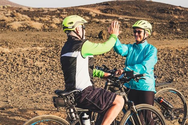 Para dwóch kaukaskich seniorów zderzyła się i dała razem pięć - jazda na rowerach - zdrowy i sprawny styl życia i koncepcja