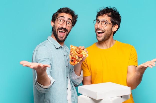 Para dwóch latynoskich przyjaciół zaskoczona miną i trzymająca pizzę na wynos